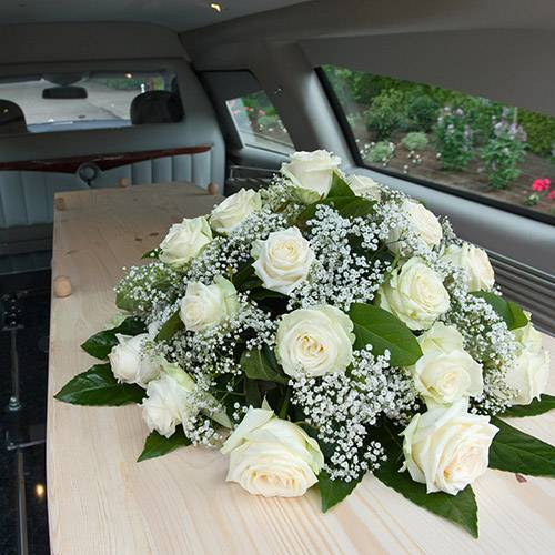 coffin with bouquet of white roses on top