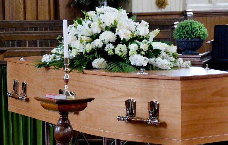 casket with flowers laid on top at a funeral ceremony